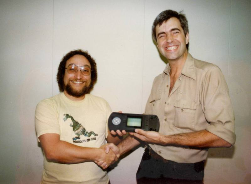 Dave Needle (left) with RJ Mical showing the Atari Lynx handheld console many years ago. (Photo from RJ Mical's Facebook page)